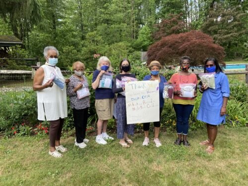 Homemade masks and sign being held by members of the Princeton Sankofa Stitchers Modern Quilt Guild and CASA staff and advisory members